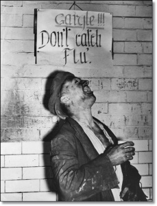 circa 1937: A miner at the Houghton Main Colliery, Yorkshire, has an anti-flu gargle after work, in front of a notice that advises him to do so, to avoid the serious epidemic that has effected miners at many neighbouring collieries. (Photo by Fox Photos/Getty Images)